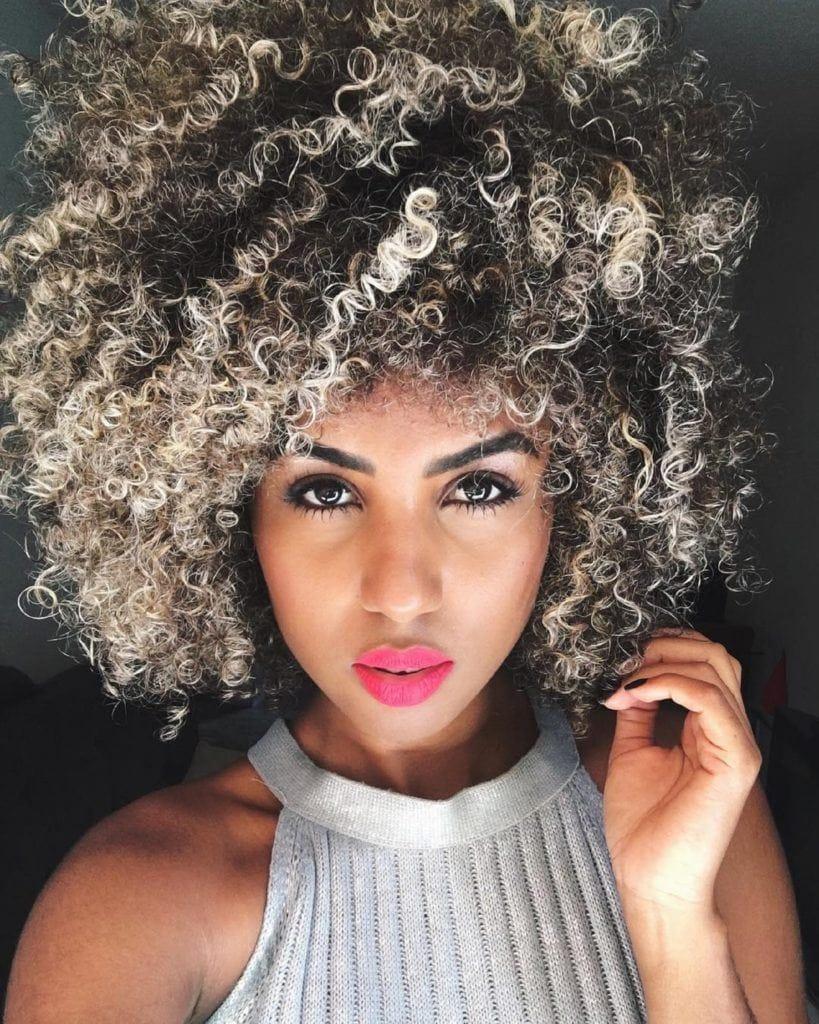 Mulher com cabelo afro e pontas platinadas