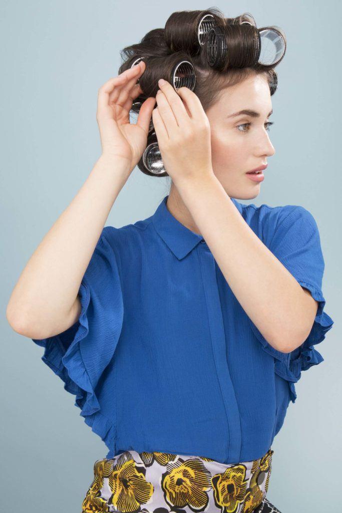 Mulher com cabelos castanho-claro usando bobes