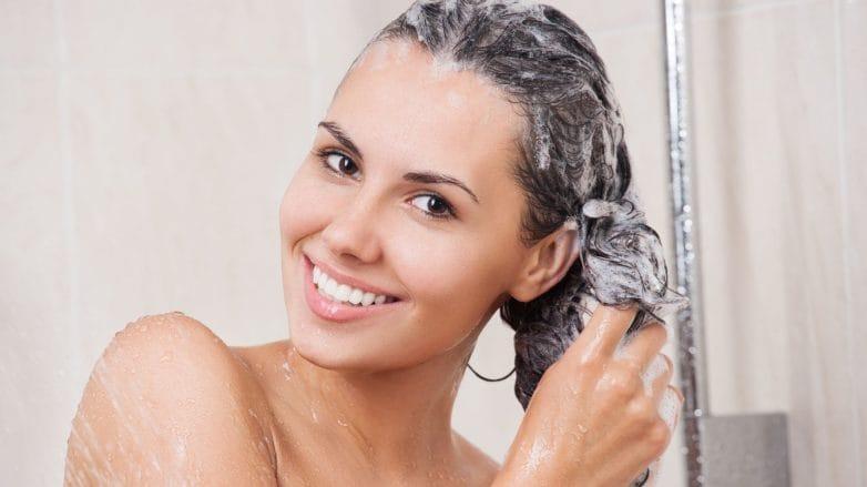 Mulher lavando o cabelo no chuveiro