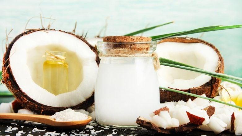 pote com óleo de coco e cocos abertos