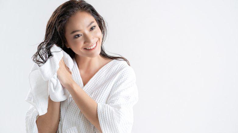 mulher de roupão secando o cabelo com toalha