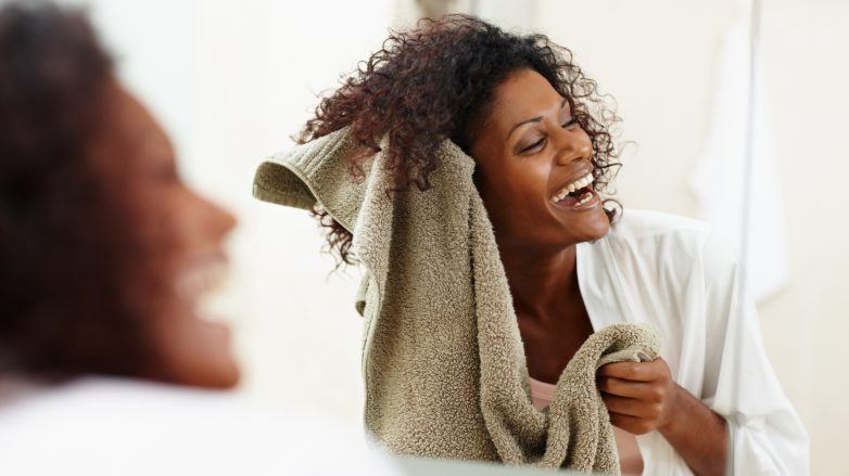 Mulher seca com toalha seus cabelos cacheados