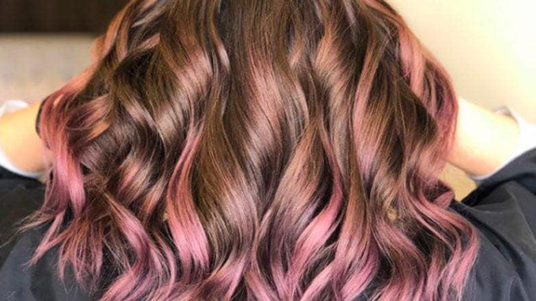 Mulher com cabelos cacheados e mechas lilás