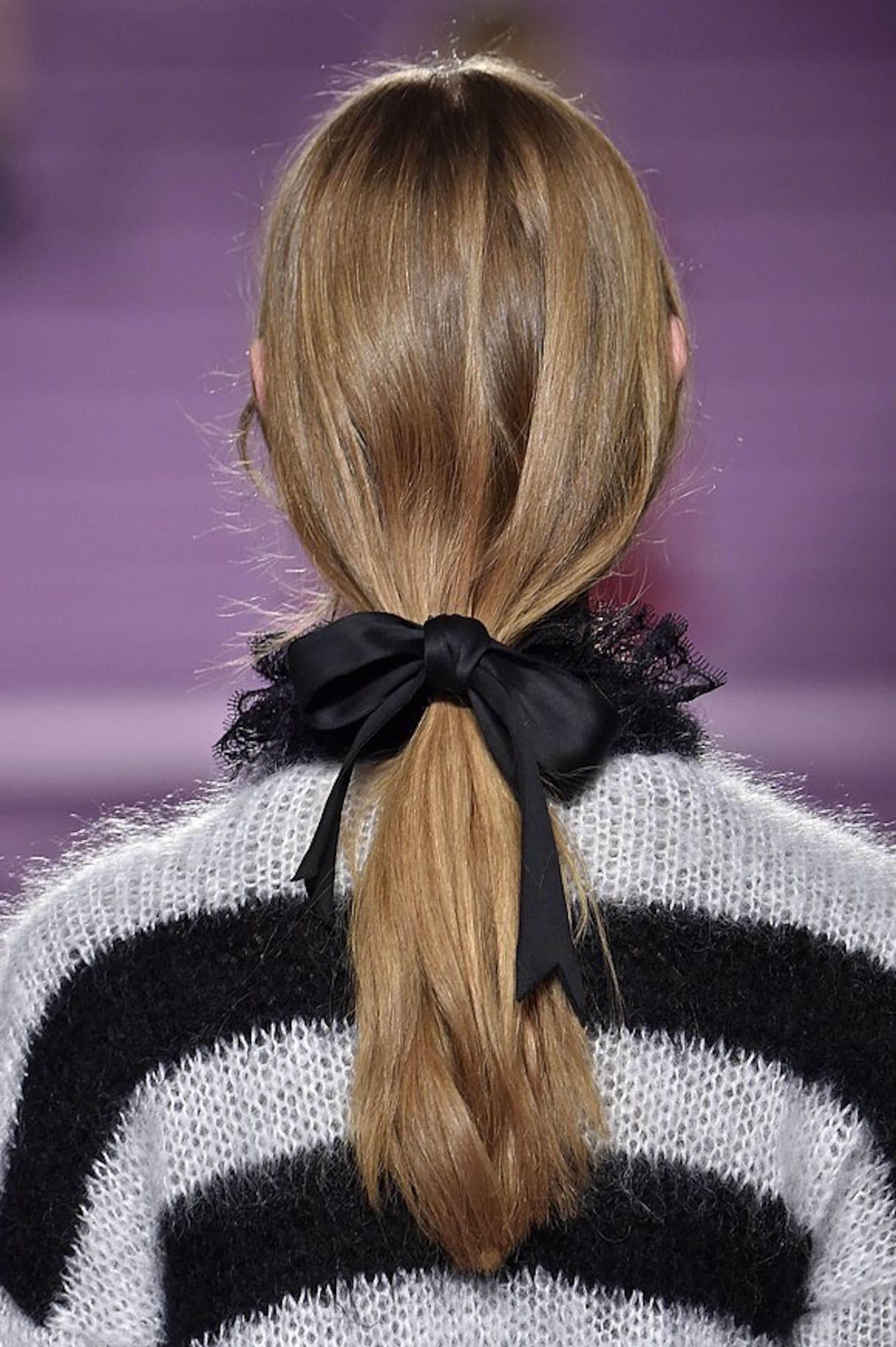 Mulher com cabelos loiros e presos por um laço