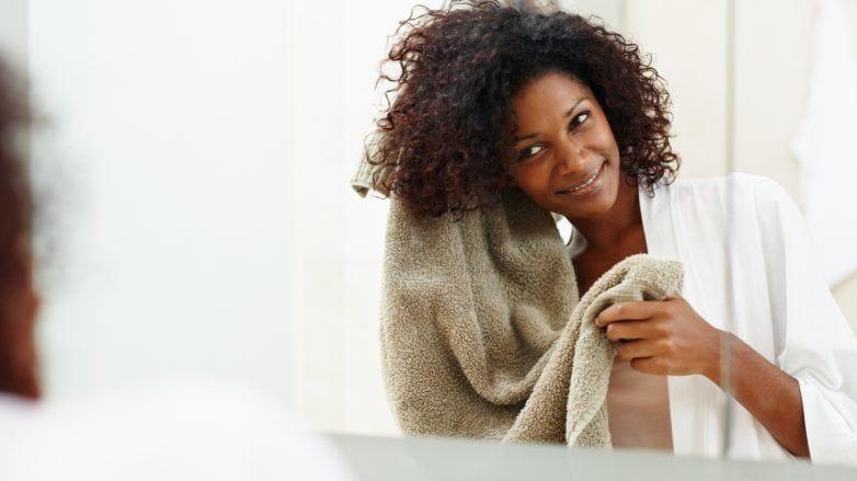 mulher enxugando o cabelo com uma toalha