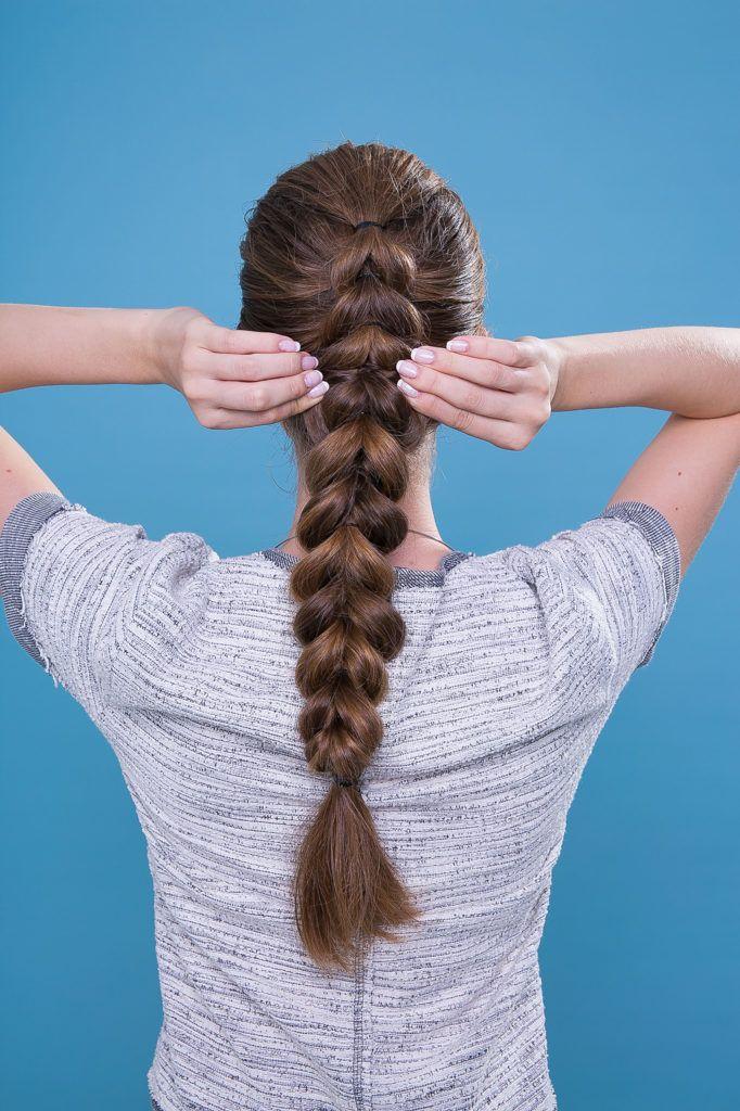 Mulher com cabelos castanho-claro fazendo trança escama de peixe
