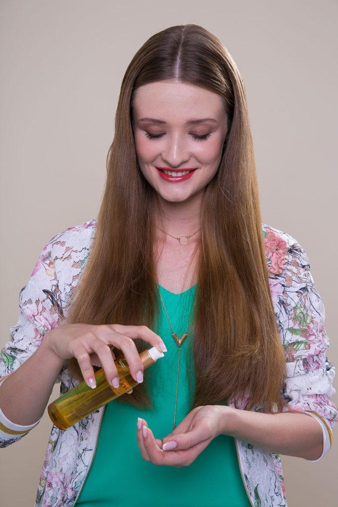 Mulher borrifando óleo nos cabelos castanho-claro e longos