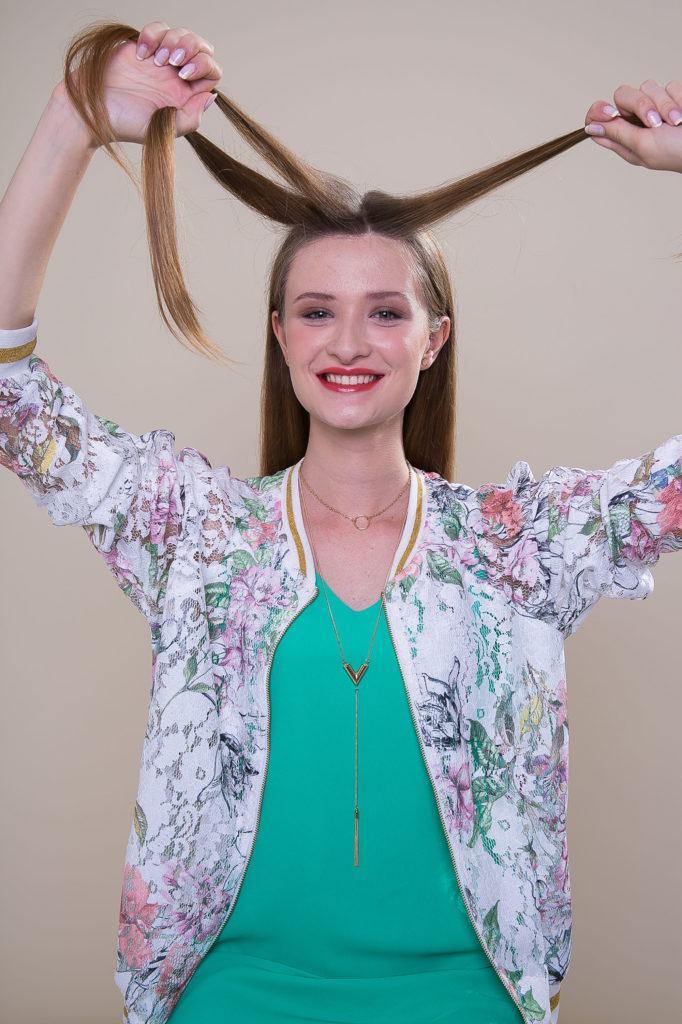 Mulher com cabelos castanho-claro fazendo trança francesa