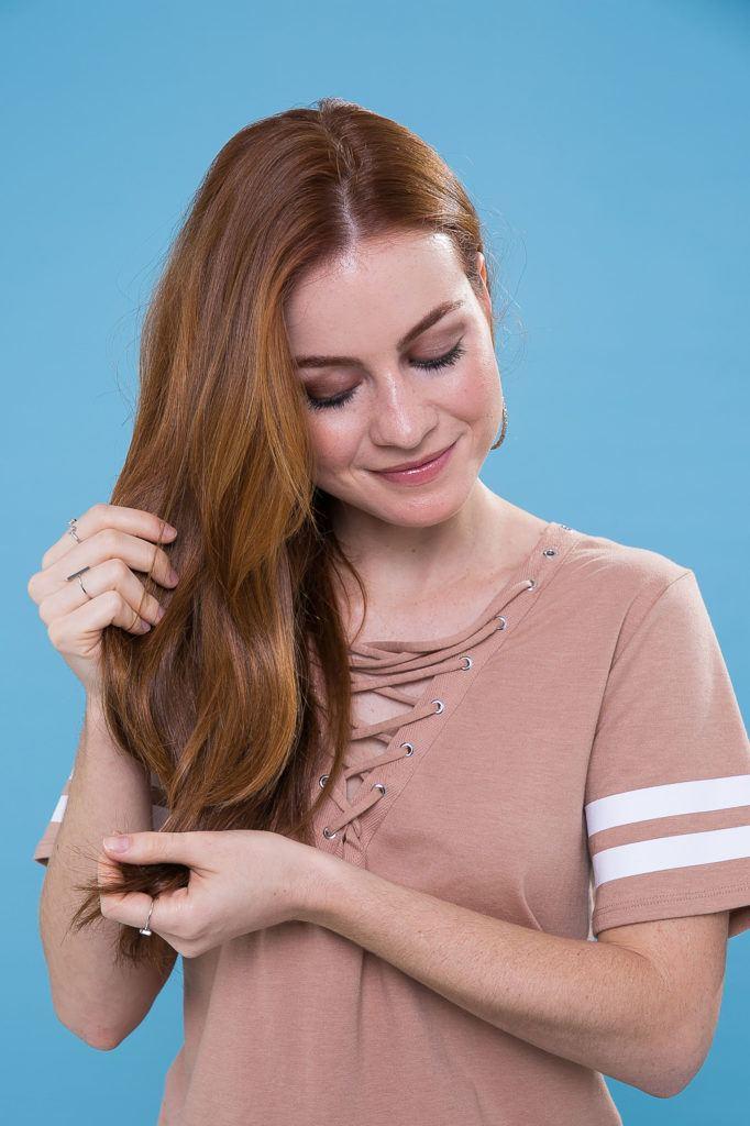 Mulher passando as mãos nos cabelos lisos e ruivos