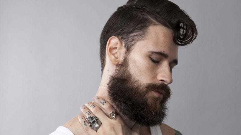 Homem com cabelo e barba pretos, topete e trança lateral