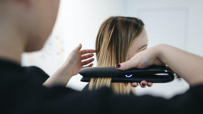 pessoa usando a chapinha para alisar cabelo de mulher