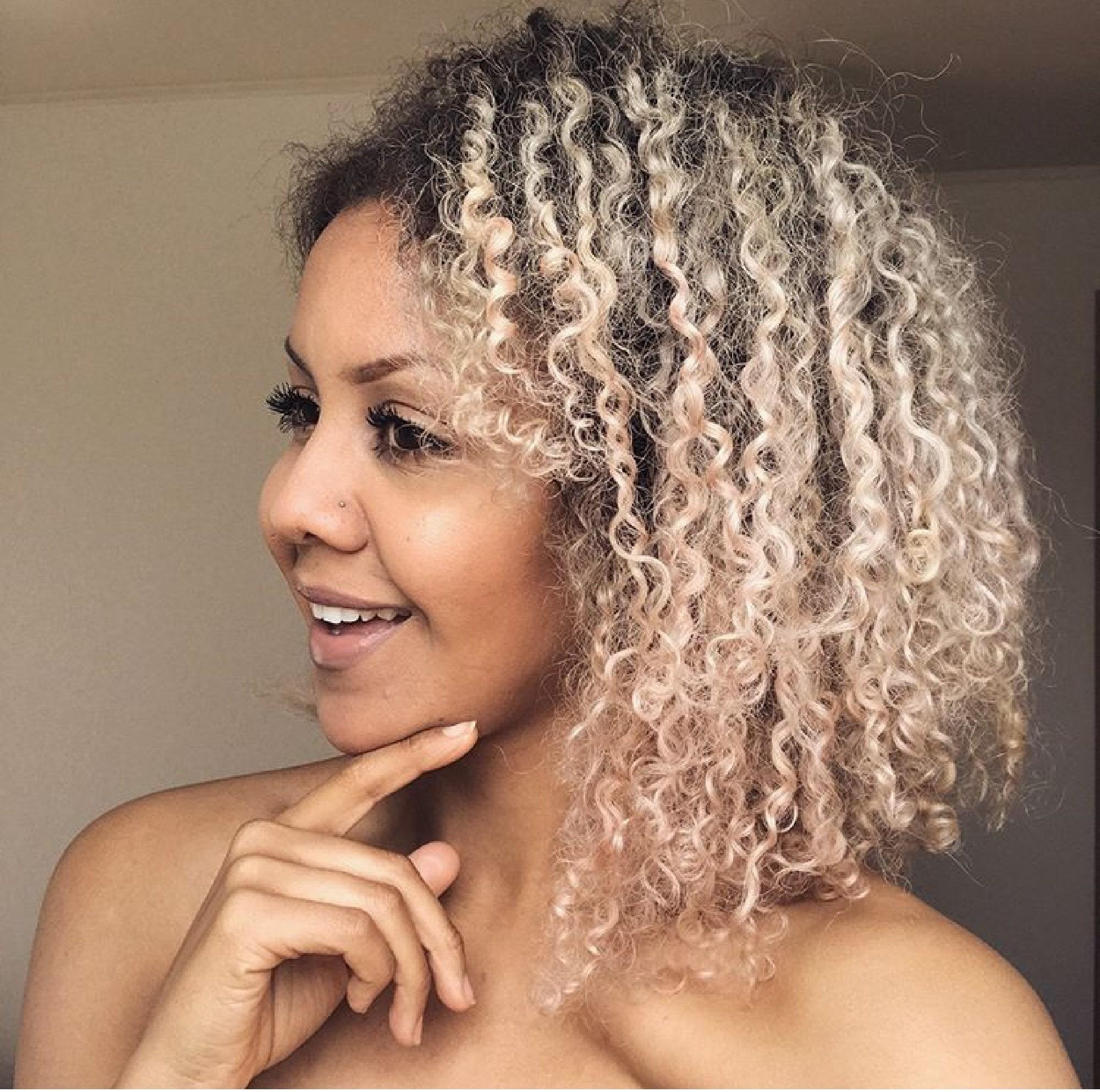 Mulher com cabelos afro e mechas loiras