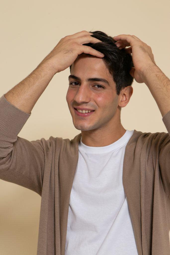 Modelo ajeitando os fios depois de ensinar como secar o cabelo com secador