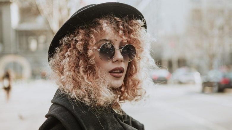 Modelo com cabelos cacheados médios e loiros + chapéu preto
