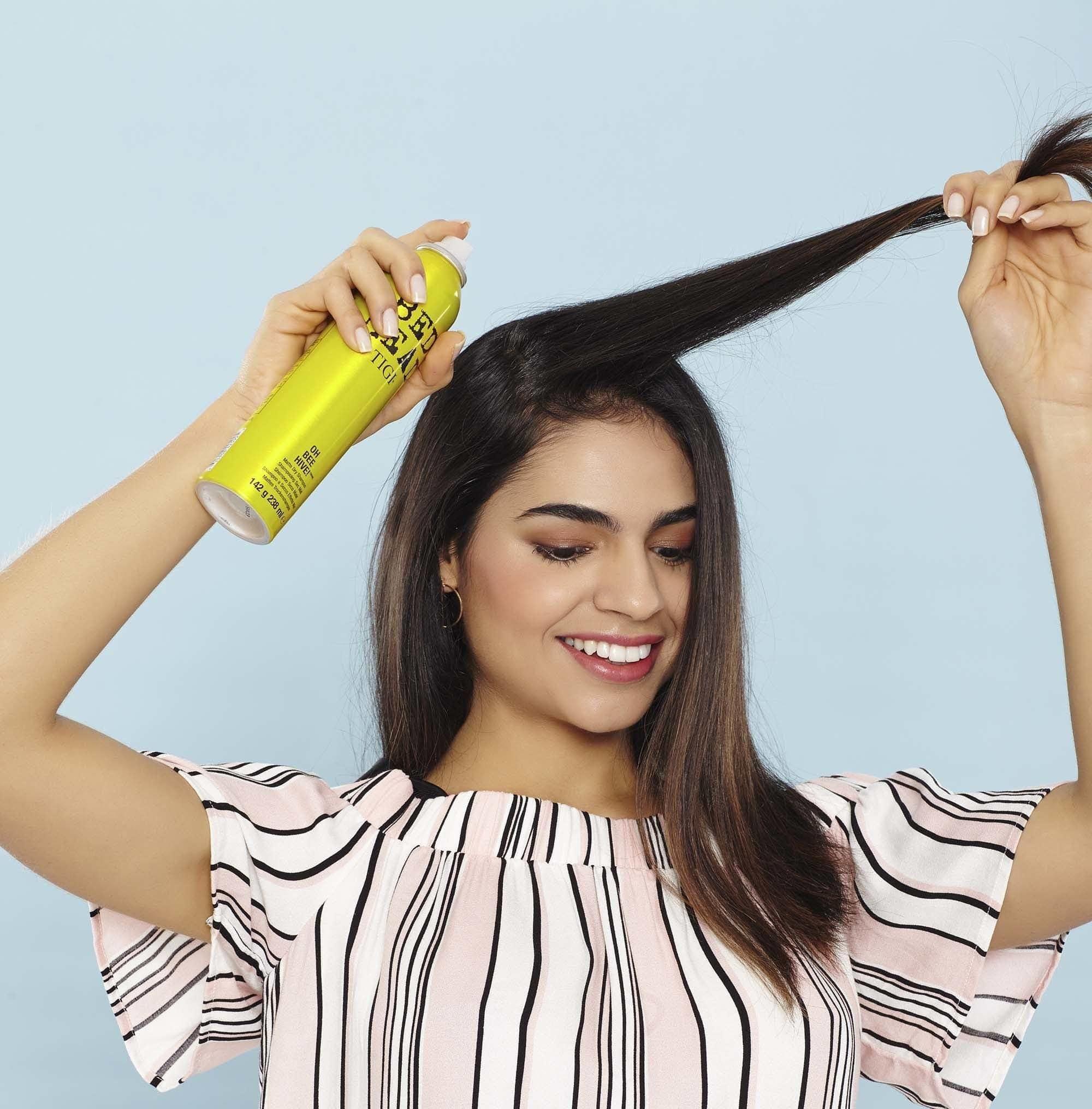 Shampoo a seco sendo aplicado em uma mecha de cabelo liso