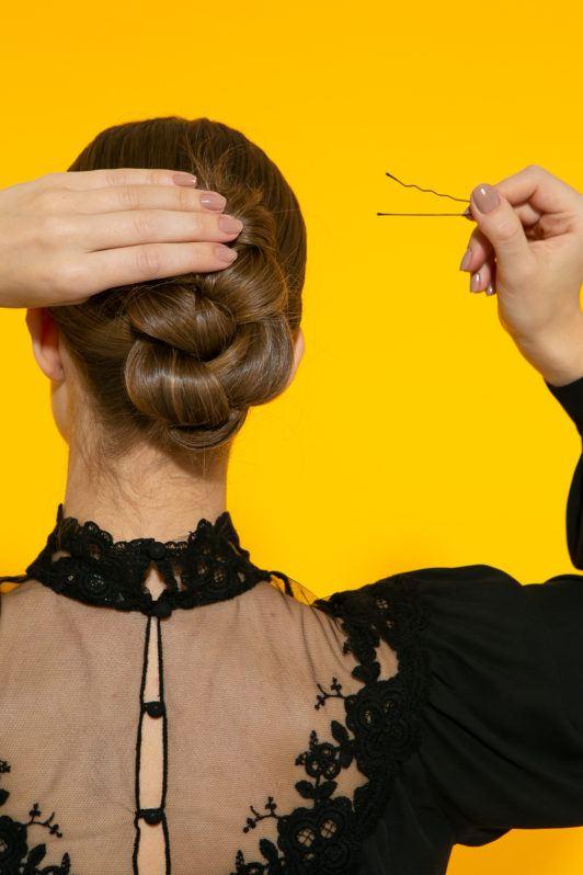 cabelo liso com coque vertical trançado sendo preso com grampo