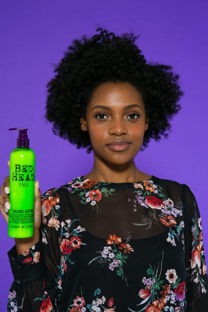 Modelo com produto na mão e blusa preta com detalhe de flores coloridas