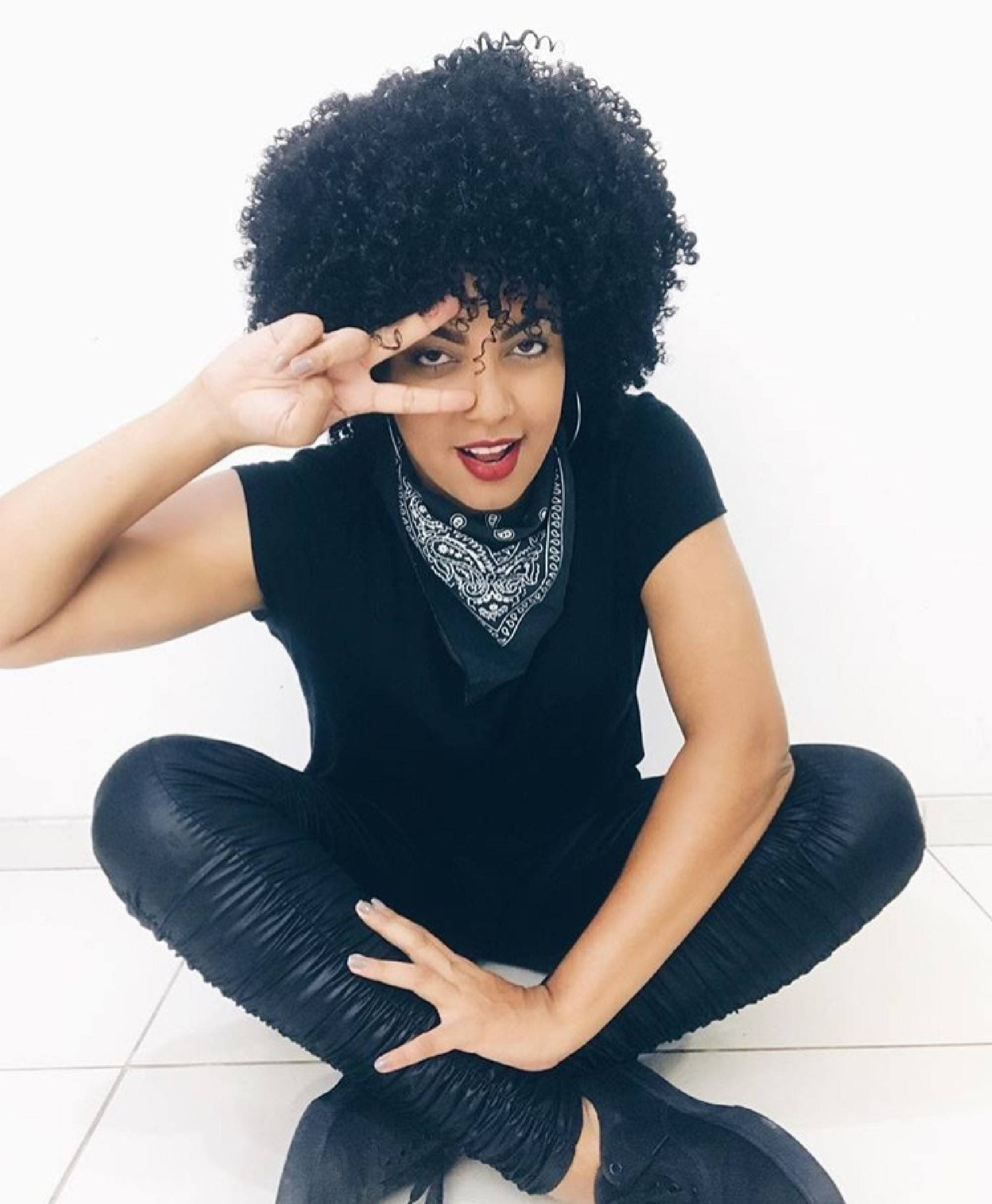 Modelo com cabelo black power preto definido com blusa preta, calça de couro preta e bandana preta no pescoço