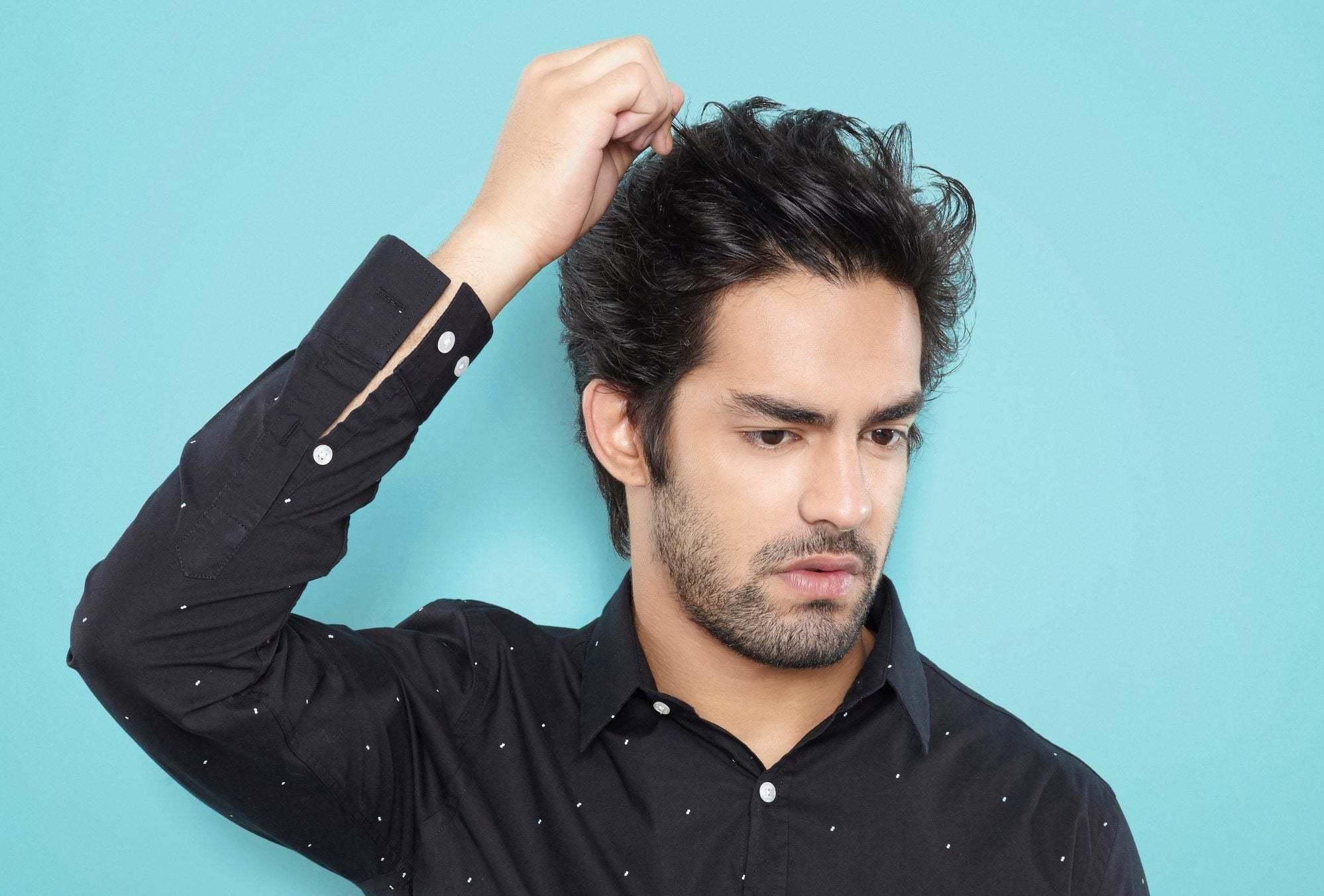 modelo masculino de cabelo liso arrepiado, com a mão na cabeça.