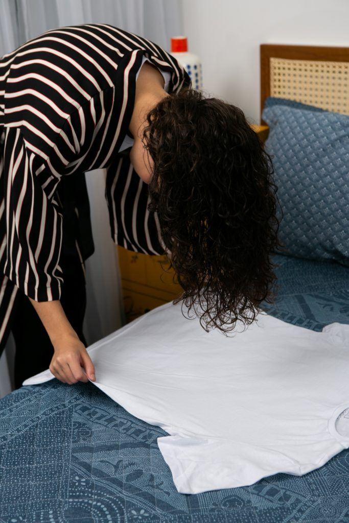 Modelo joga todo o cabelo sobre uma toalha que está na cama.