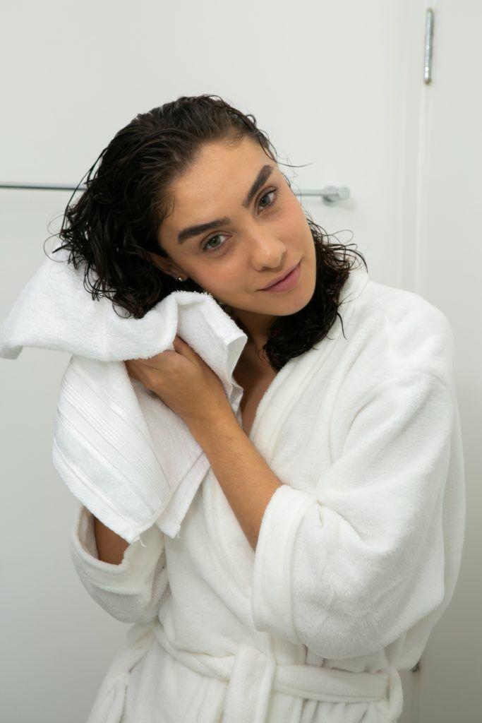modelo seca os fios cacheados com uma toalha branca.