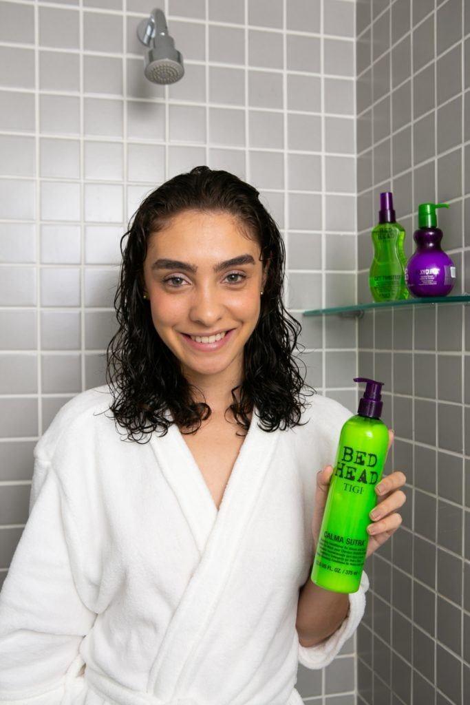 modelo no banheiro, de cabelo molhado, segura o Co Was Bed Head Calma Sutra