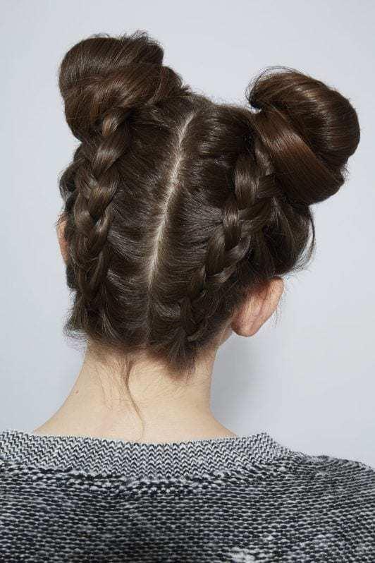 modelo de cabelo castanho com meio coque trançado.