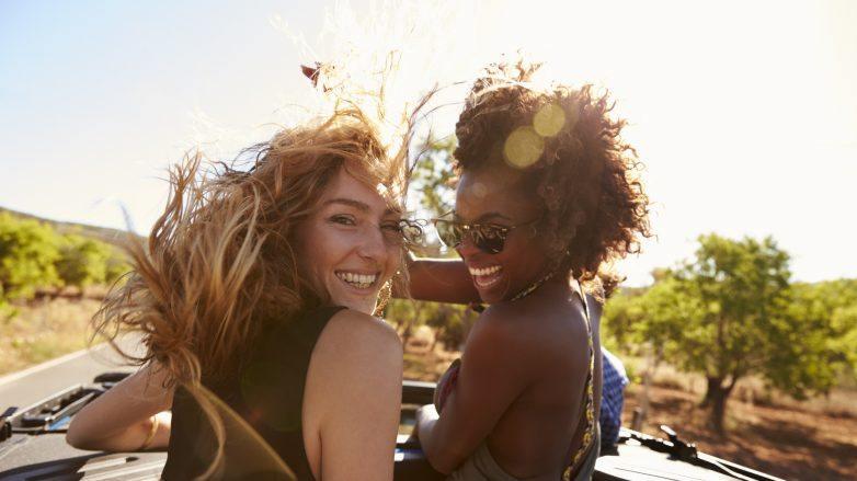 Duas mulheres dentro de um carro com cabelos ao vento no verão