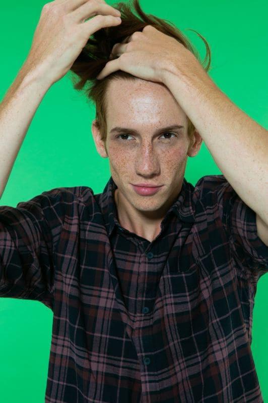 modelo masculino penteando os cabelos com os dedos.