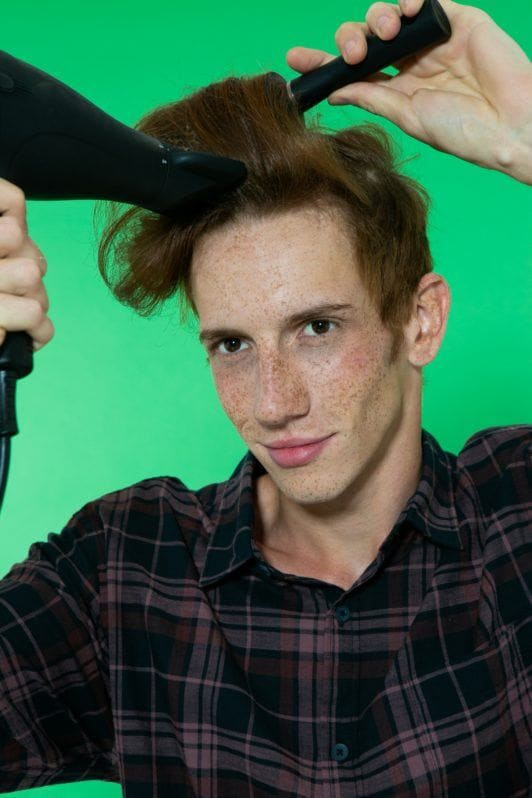 Modelo de cabelo ruivo escovando o cabelo