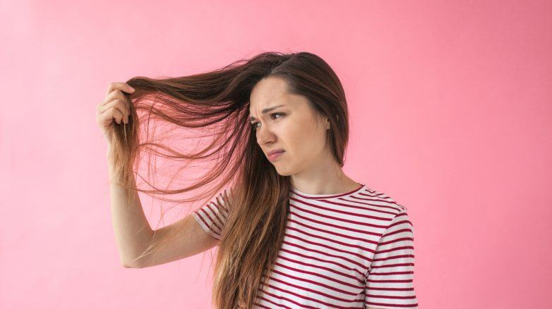 mulher olhando para o cabelo insatisfeita
