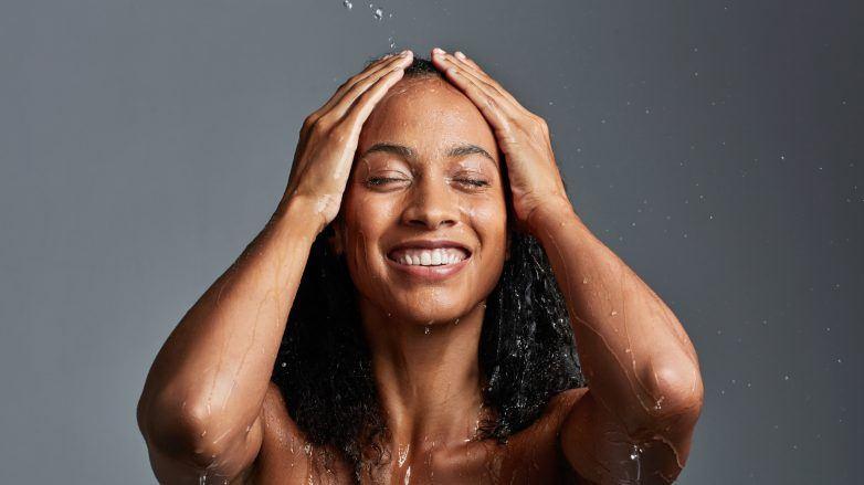Mulher com cabelos cacheados lava o cabelo