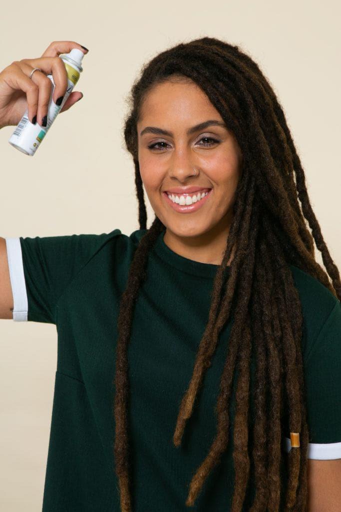 Modelo aplica shampoo a seco nos dios para estilizar dreadlocks