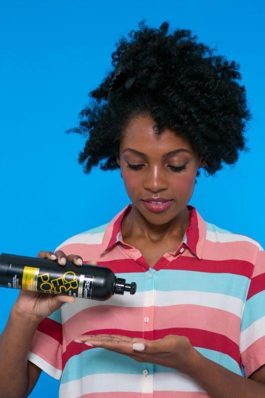 modelo de cabelo crespo aplicando o Creme de Pentear TRESemmé Crespos para pentear cabelo afro