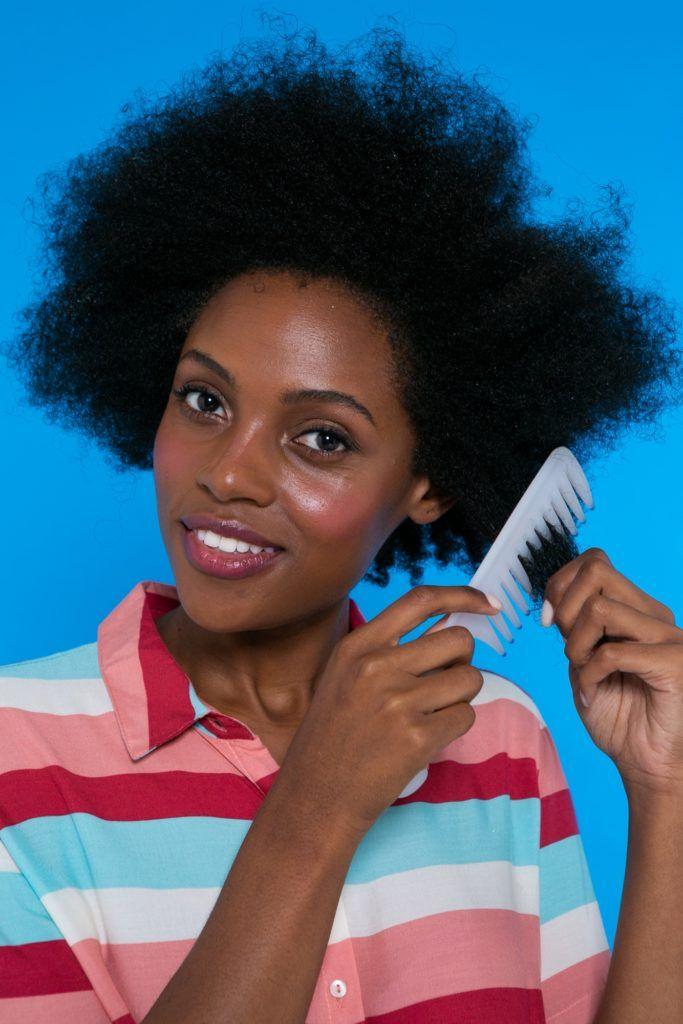 modelo de cabelo crespo penteando o com pente de dente largo