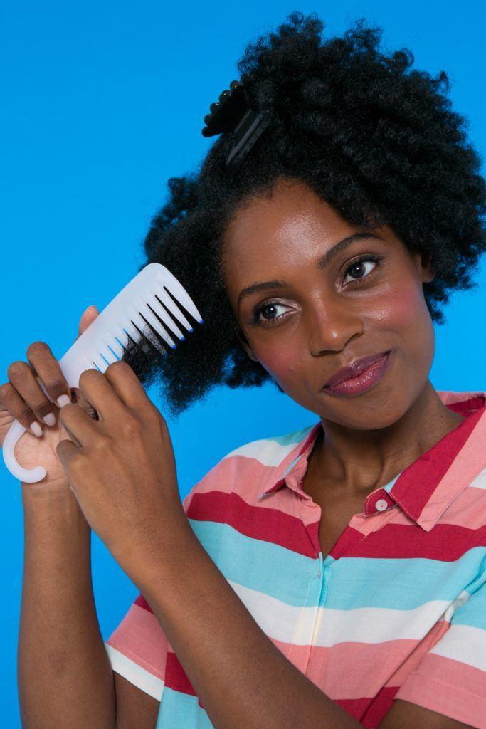 modelo de cabelo crespo penteando o cabelo afro com pente largo