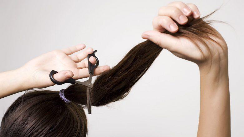 Mulher cortando o cabelo preso em um rabo de cavalo com tesoura
