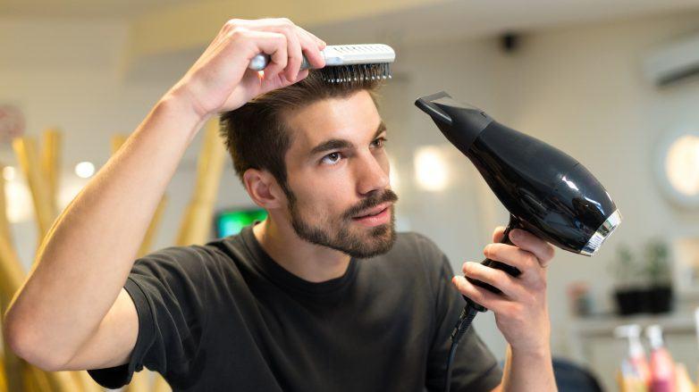 Homem penteia e seca o cabelo com secador