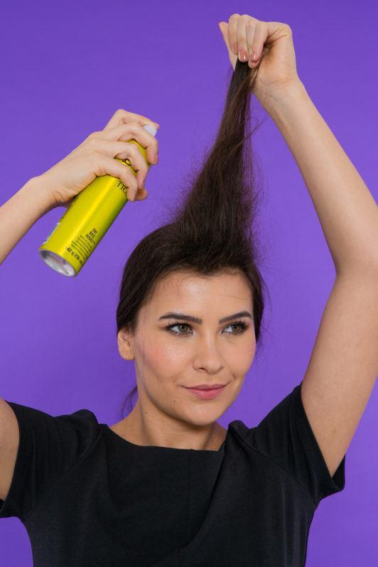 Modelo aplica shampoo seco para fazer trança com topete
