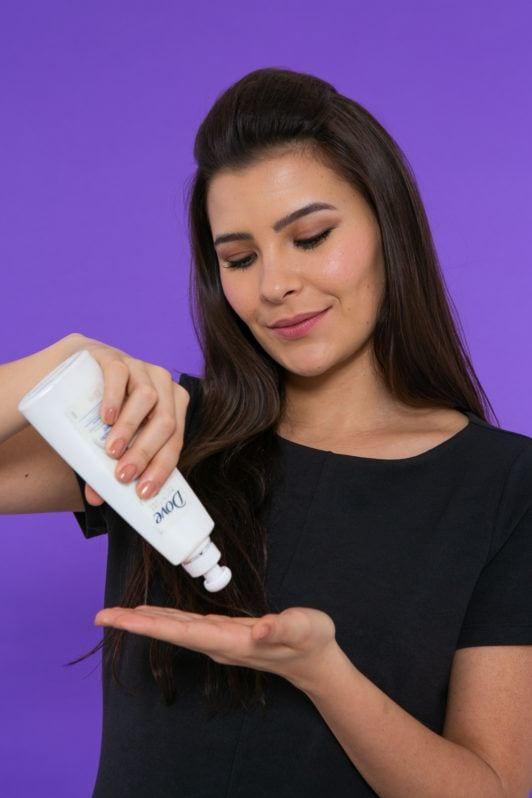 Modelo aplica creme de pentear para fazer trança com topete