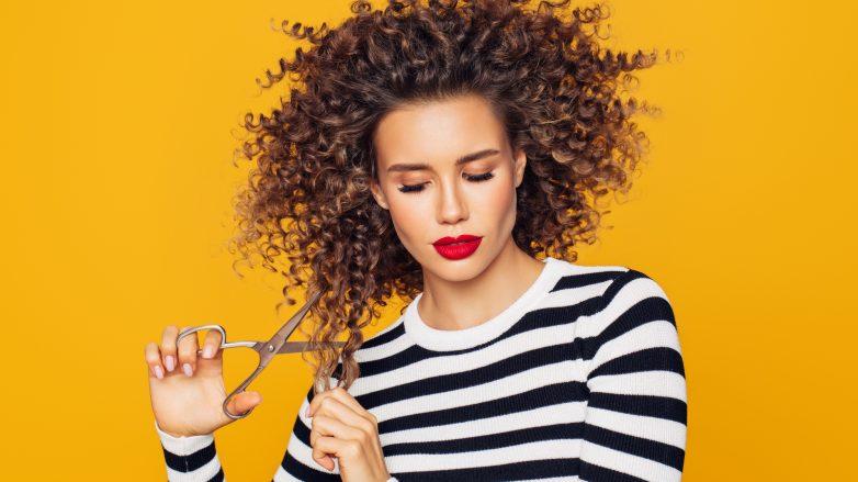 Mulher com cabelos cacheados corta o cabelo sozinha com tesoura