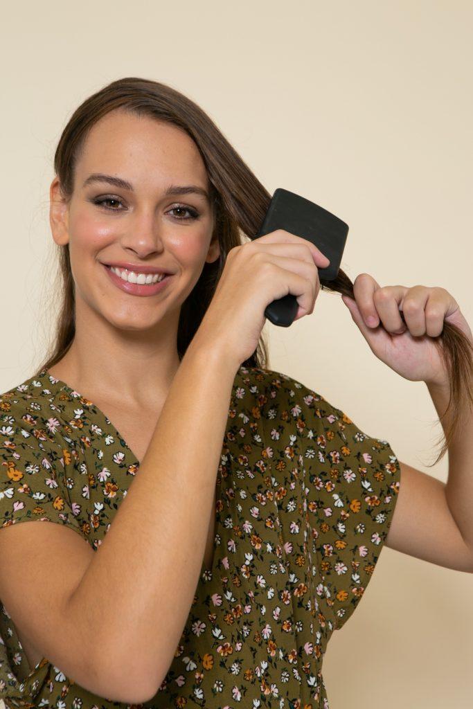 Modelo penteia os cabelos para alisar os fios naturalmente