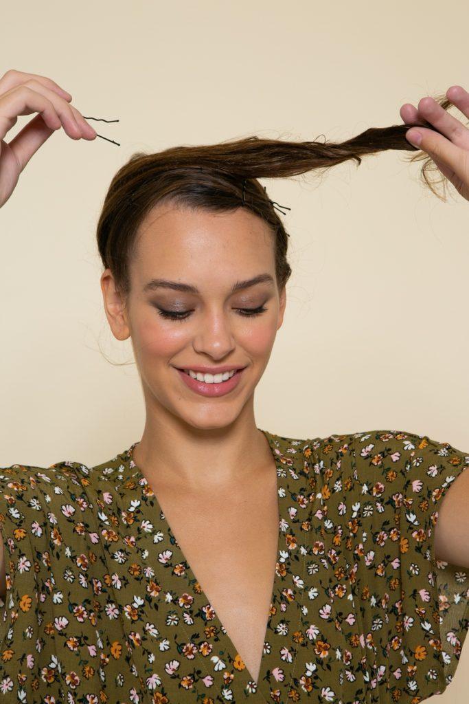 Modelo prende os cabelos com grampo para alisar os fios naturalmente