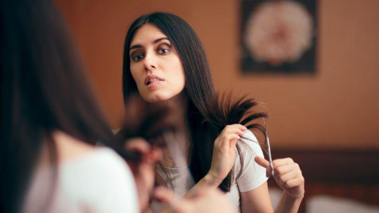 mulher de cabelo castanho longo cortando cabelo sozinha