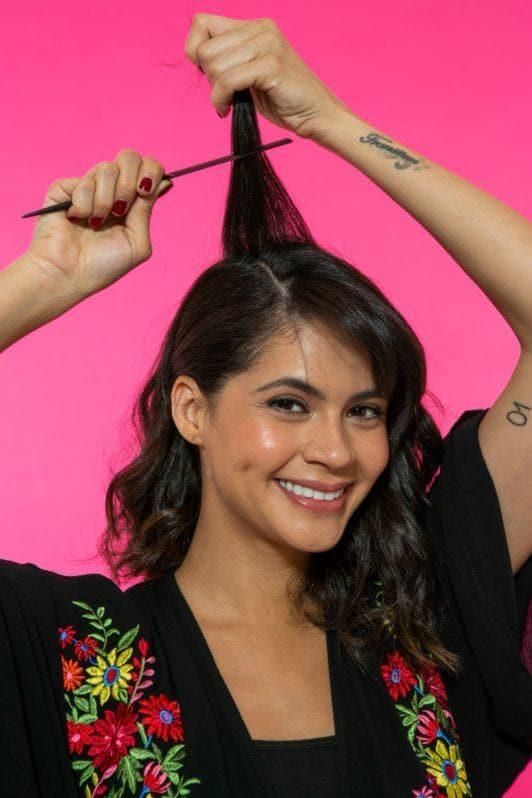 modelo de cabelo médio desfiando os fios com um pente fino.