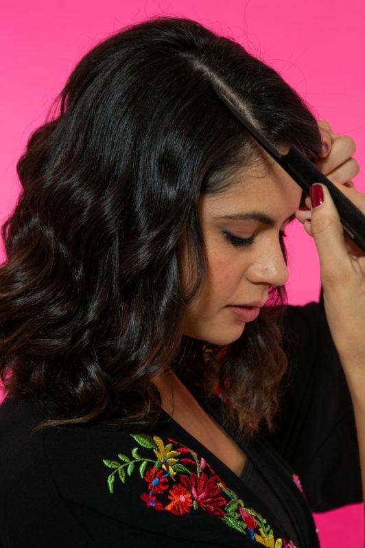 modelo de cabelo de comprimento médio ondulado repartindo os fios de lado com um pente fino