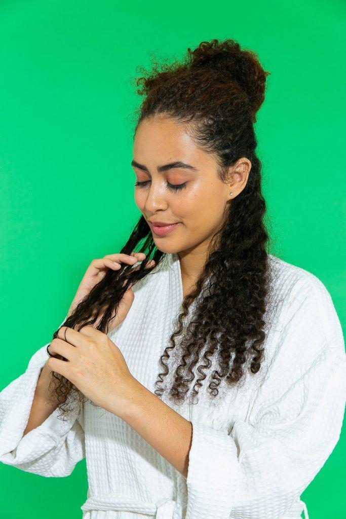 Mulher com cabelo cacheado longo aplicando produto