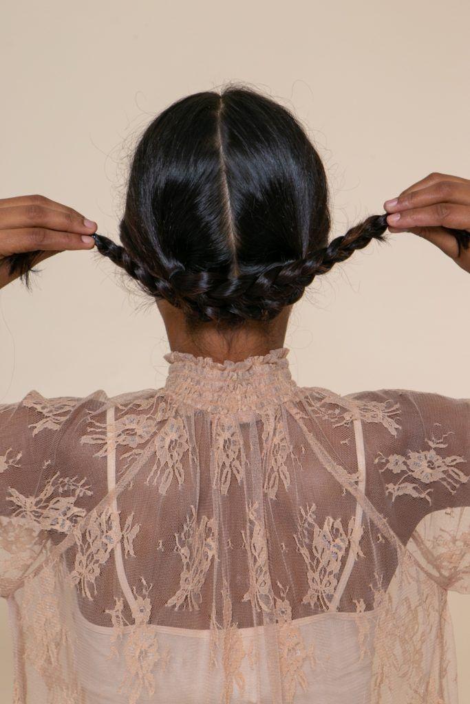modelo morena de cabelo preto longo e levemente ondulado cruzando duas tranças