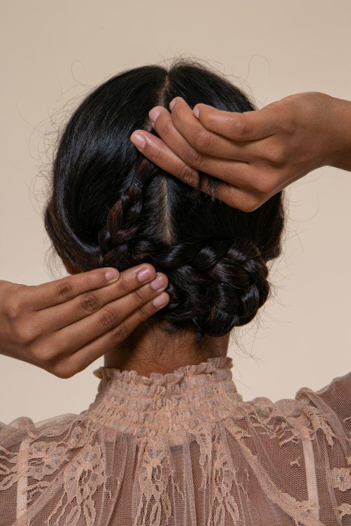 modelo morena de cabelo preto longo e levemente ondulado prendendo tranças cruzadas para o penteado de noiva