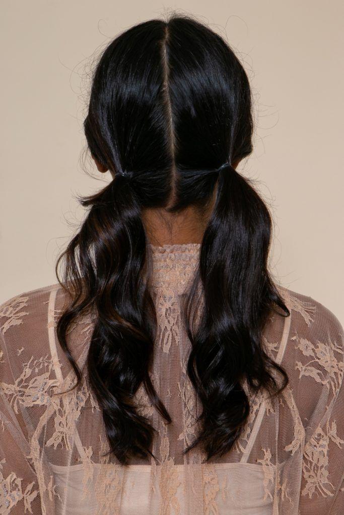 modelo morena de cabelo preto longo e levemente ondulado com dois rabos de cavalo baixos